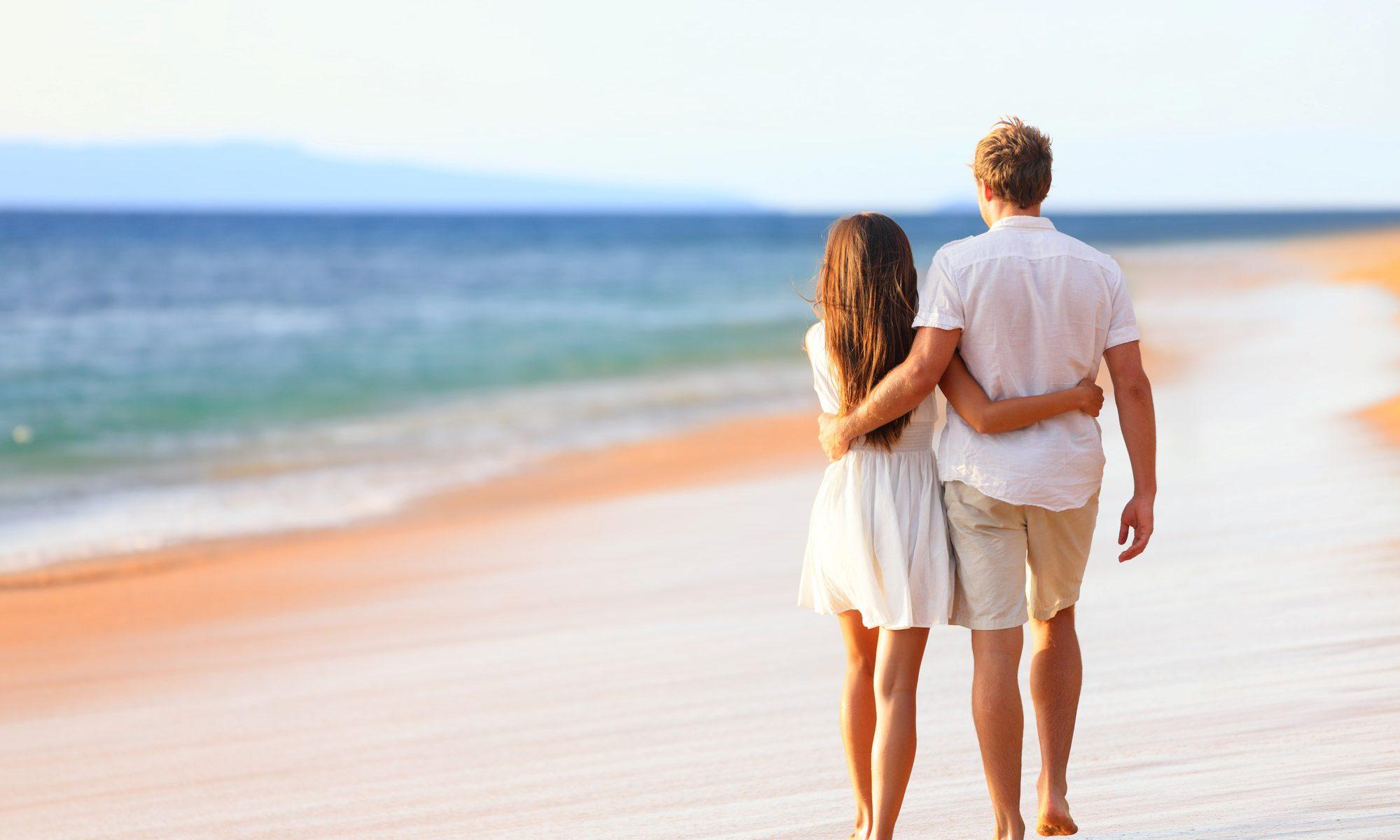 Beach couple walking on romantic travel