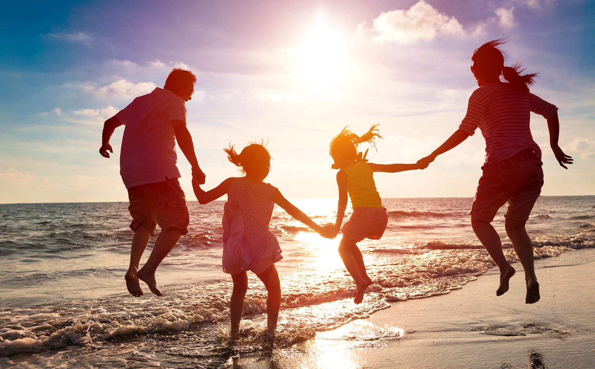 family at beach jumping
