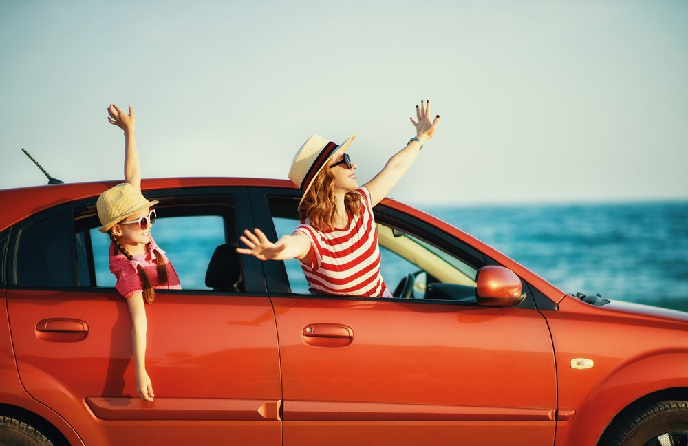 happy family mother and child girl goes to summer travel trip in car