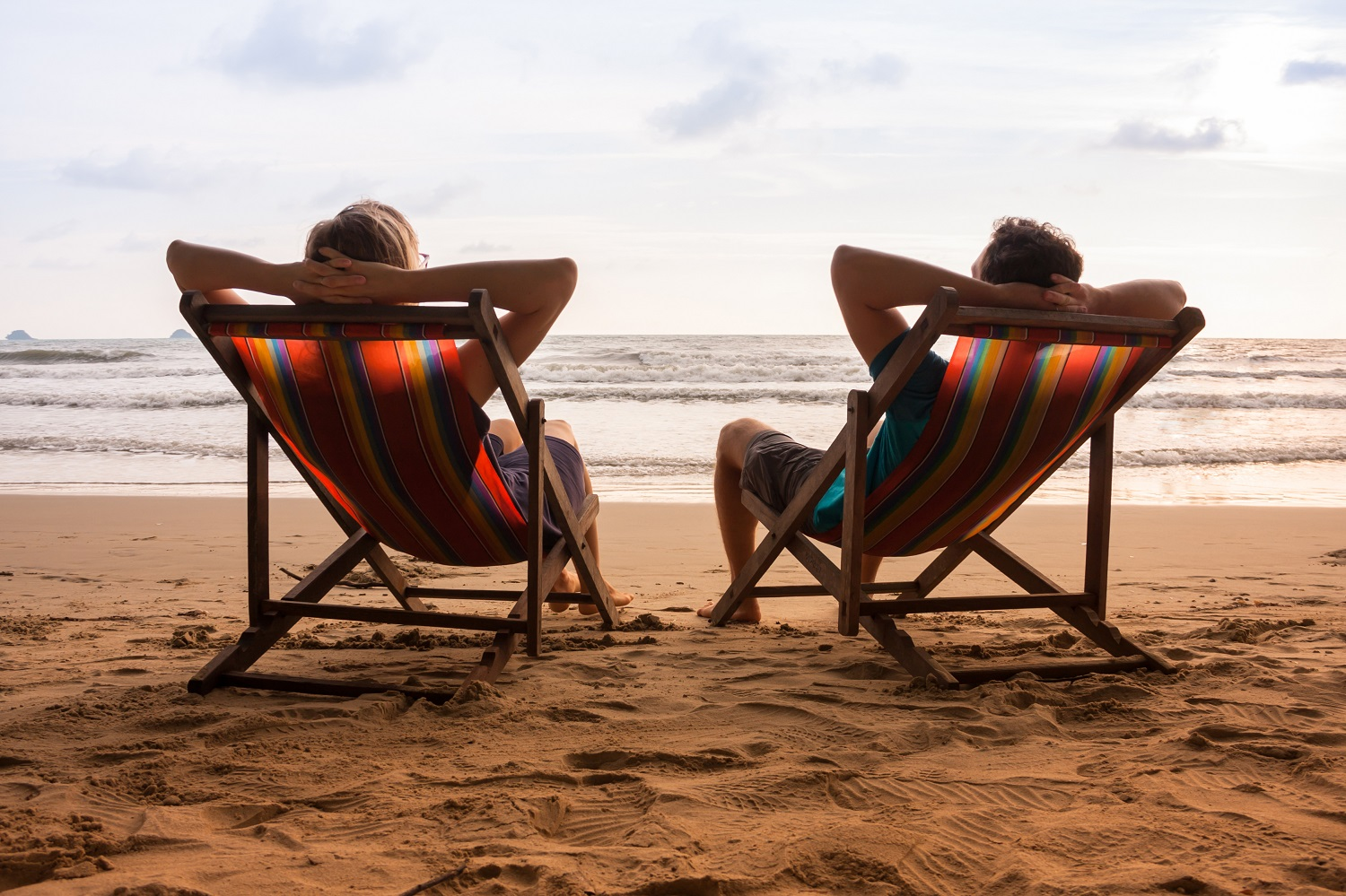 Couple in deck chairs at sea beach
